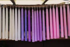 Velas multicoloras que cuelgan en una cuerda en fila Fotos de archivo libres de regalías