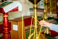 Velas na adoração da igreja Obscuridade, mão Imagens de Stock Royalty Free
