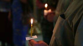 Velas nas mãos dos crentes na igreja ortodoxa do russo filme