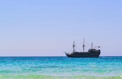 Velas negras del barco pirata a lo largo de la costa Foto de archivo