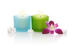 Velas, orquídea e alguns seixos brancos Imagens de Stock