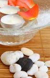 Velas, pétalos de rosas en tazón de fuente y piedras en bambú Fotografía de archivo libre de regalías