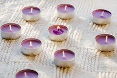 Velas pequeñas, púrpuras, aromáticas en un fondo blanco imagen de archivo