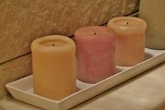 Velas perfumadas amarillas y rosadas en un primer blanco del soporte imagen de archivo libre de regalías