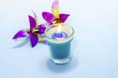 Velas perfumadas azules claras en fondo del azul de la pendiente Fotografía de archivo