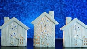 Velas que ardem na casa branca do castiçal no brilho azul das luzes Blurred filme
