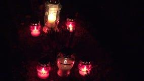Velas que queimam-se em sepulturas no cemitério na noite Tudo Hallows a véspera 4K vídeos de arquivo