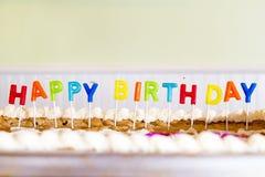 Velas que soletram o feliz aniversario que cola em um bolo da cookie Foto de Stock Royalty Free