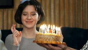 Velas que soplan de la chica joven en la torta de cumpleaños Fotos de archivo