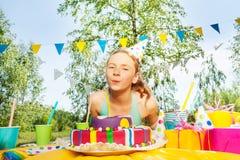 Velas que soplan de la chica joven feliz en la torta de cumpleaños Fotos de archivo