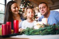 Velas que soplan de la familia joven en la guirnalda del advenimiento Imágenes de archivo libres de regalías