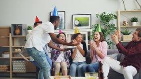 Velas que soplan de la muchacha del cumpleaños en la torta cuando amigos que lanzan aplaudir del confeti almacen de metraje de vídeo