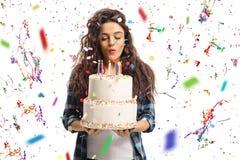 Velas que soplan del adolescente en una torta de cumpleaños con el st del confeti Foto de archivo libre de regalías