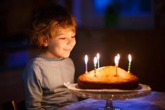 Velas que soplan del muchacho del niño en la torta de cumpleaños Imágenes de archivo libres de regalías