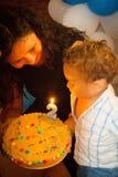 Velas que soplan del niño en la torta de cumpleaños Imagenes de archivo