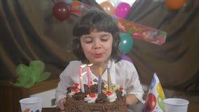 Velas que soplan en una torta de cumpleaños, cámara lenta de la muchacha hermosa joven almacen de metraje de vídeo
