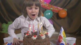 Velas que soplan en una torta de cumpleaños, cámara lenta de la muchacha hermosa joven almacen de video