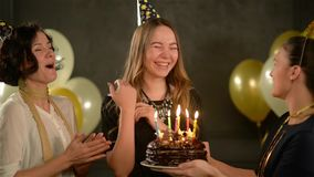 Velas que soplan sonrientes de la muchacha bonita en una torta de chocolate, divirtiéndose con sus dos amigos Mujeres que cantan  almacen de metraje de vídeo