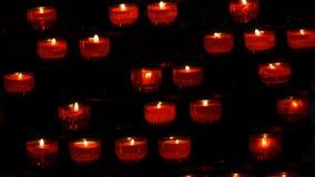 Velas redondas vermelhas de queimadura na igreja Católica vídeos de arquivo