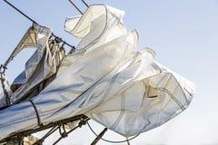Velas Reefed e céu azul imagens de stock royalty free