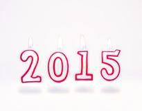 Velas rojas ardientes con el número 2015 que vuela en el fondo blanco Foto de archivo