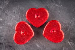 Velas rojas bajo la forma de corazones en un fondo gris El símbolo del día de amantes Día de tarjeta del día de San Valentín Conc Foto de archivo libre de regalías