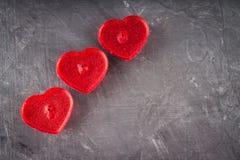 Velas rojas bajo la forma de corazones en un fondo gris El symb Imágenes de archivo libres de regalías