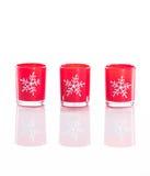 3 velas rojas, candeleros con los copos de nieve cristalinos aislados en fondo blanco reflexivo del plexiglás Fotografía de archivo