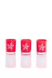 3 velas rojas, candeleros con los copos de nieve cristalinos aislados en fondo blanco reflexivo del plexiglás con el espacio de l Foto de archivo libre de regalías