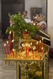 Velas rojas de la cera en una palmatoria en la iglesia ortodoxa Foto de archivo libre de regalías