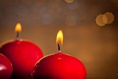 Velas rojas de la Navidad en fondo de oro del bokeh Fotos de archivo