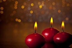 Velas rojas de la Navidad en fondo de oro del bokeh Fotografía de archivo