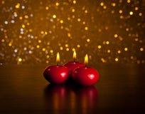 Velas rojas de la Navidad en fondo de oro del bokeh de la tabla de madera Imagenes de archivo