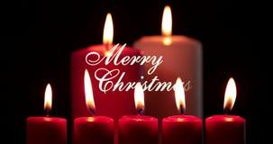 Velas rojas de la Navidad y texto de la Feliz Navidad almacen de metraje de vídeo