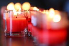 Velas rojas del rezo del primer en pequeños vidrios en iglesia católica Fotos de archivo