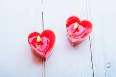 Velas rojas en forma de corazón en el fondo de madera blanco Fotografía de archivo libre de regalías