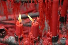 Velas rojas que queman en una capilla budista Foto de archivo