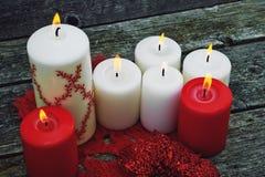 Velas rojas y blancas ardientes en el fondo de madera Fotografía de archivo libre de regalías