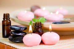 Velas rosadas, piedras, y petróleo esencial. Foto de archivo libre de regalías