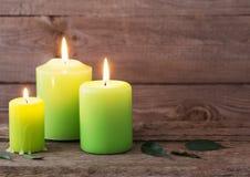 Velas verdes no fundo de madeira escuro Imagem de Stock