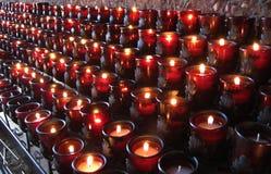 Velas vermelhas abundantes da igreja Fotografia de Stock