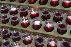 Velas vermelhas em uma igreja Católica Imagem de Stock