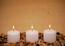 Velas votivas blancas en la configuración del zen en la arpillera Foto de archivo