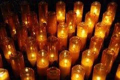 Velas votivas del rezo de la iglesia en tarros Fotos de archivo