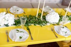 Velas y cubiletes en una tabla que se casa adornada Foco selectivo imagen de archivo libre de regalías