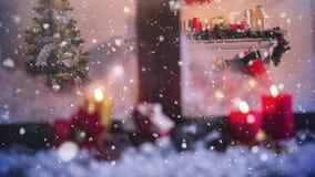 Velas y decoración de la Navidad fuera de una ventana combinada con nieve que cae