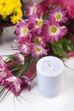 Velas y flores aisladas en blanco Imagenes de archivo