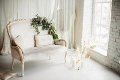 Velas y flores en el sofá Fotografía de archivo libre de regalías
