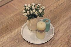 Velas y rosas en un florero en una tabla de madera Imagenes de archivo
