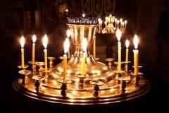 Velas y una lámpara que quema en la iglesia. Imagenes de archivo